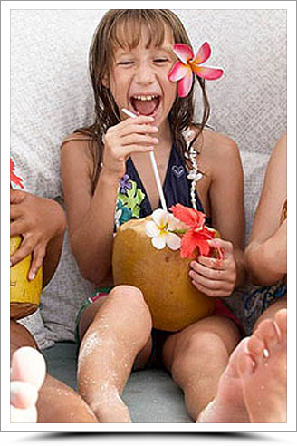 Young Girl laughing drinking from a coconut with a straw