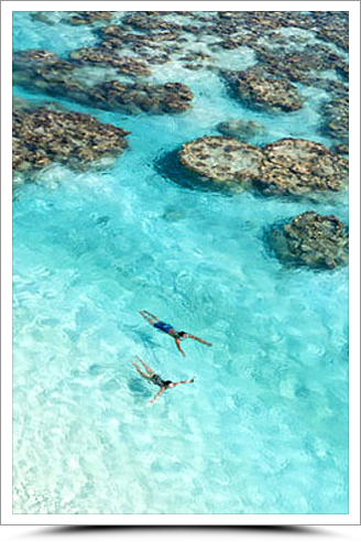 Couple swimming in Tetiaroa lagoon at The Brando